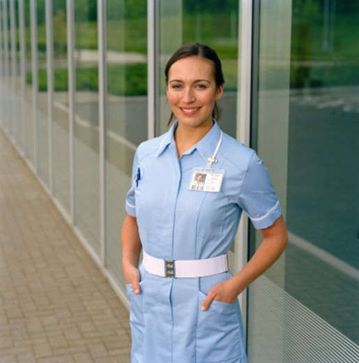 Female nurse by building, smiling, portrait : Stock Photo