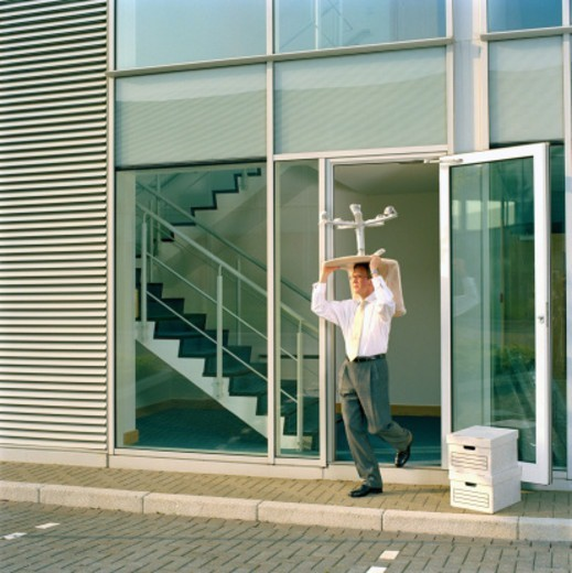 Stock Photo: 1527R-1115100 Businessman carrying chair above head by doorway of building