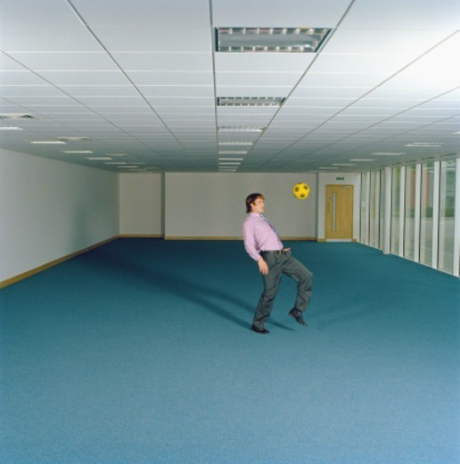 Businessman in empty office, playing with football : Stock Photo