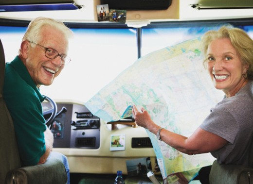 Stock Photo: 1527R-1115226 Senior couple with map, sitting in motor home, portrait