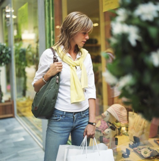 Woman carrying shopping bags, looking at retail window display : Stock Photo