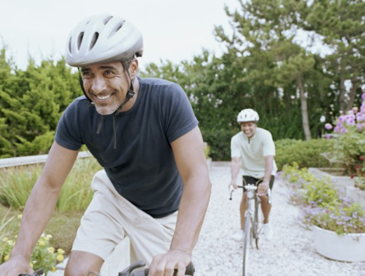 Stock Photo: 1527R-1116822 Two mature men riding bicycles, smiling
