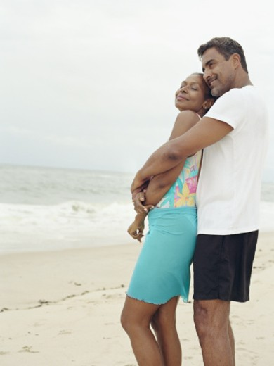 Mature couple embracing at beach, side view : Stock Photo
