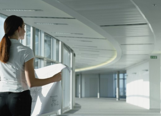 Stock Photo: 1527R-1117107 Business woman standing in corridor, holding plans, rear view