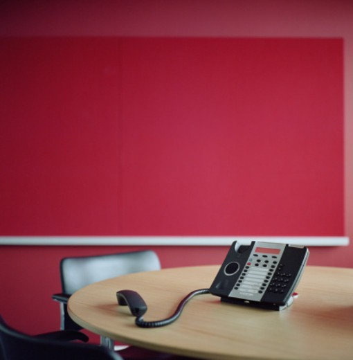 Telephone with receiver off hook, on conference room table : Stock Photo