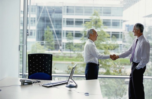 Stock Photo: 1527R-1117234 Two businessmen shaking hands in office by window, side view