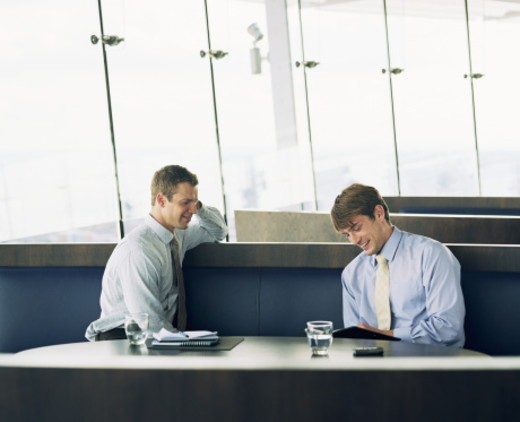 Stock Photo: 1527R-1117335 Two seated businessmen, smiling