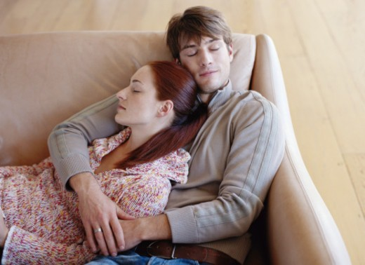 Young couple embracing on sofa, eyes closed, elevated view : Stock Photo