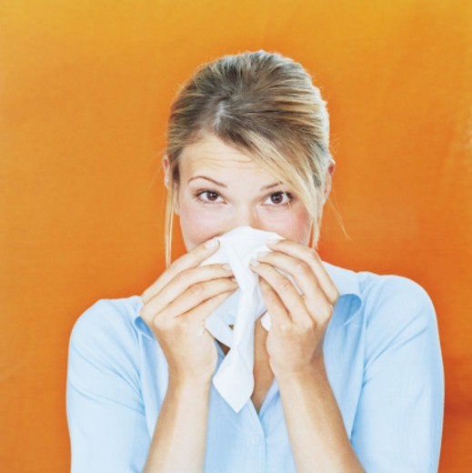 Stock Photo: 1527R-1117557 Woman blowing nose on tissue, portrait, close-up