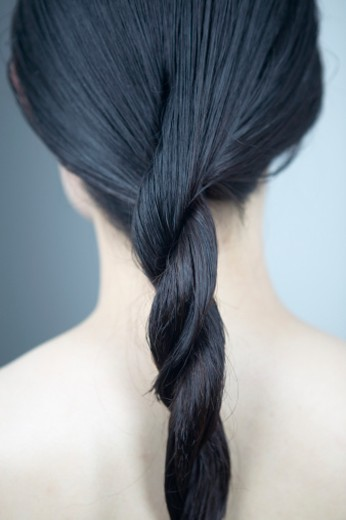 Stock Photo: 1527R-1117913 Young woman with hair twisted, rear view