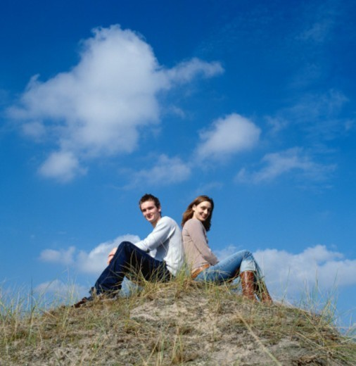 Young man and woman sitting back to back, smiling, portrait : Stock Photo