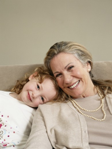 Mature woman and grandaughter (3-5) on sofa, smiling, portrait : Stock Photo