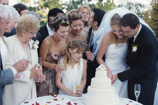 Guests watching bride and groom cut cake at wedding reception : Stock Photo