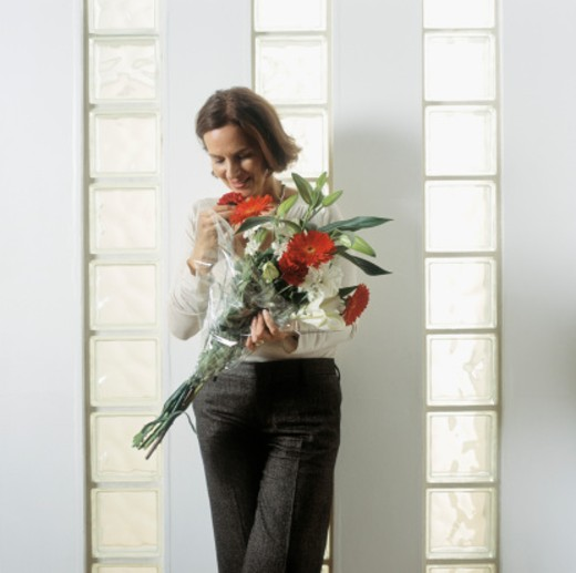 Mature woman holding bouquet of flowers : Stock Photo