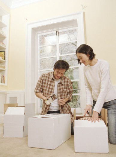 Couple taping up boxes in home : Stock Photo