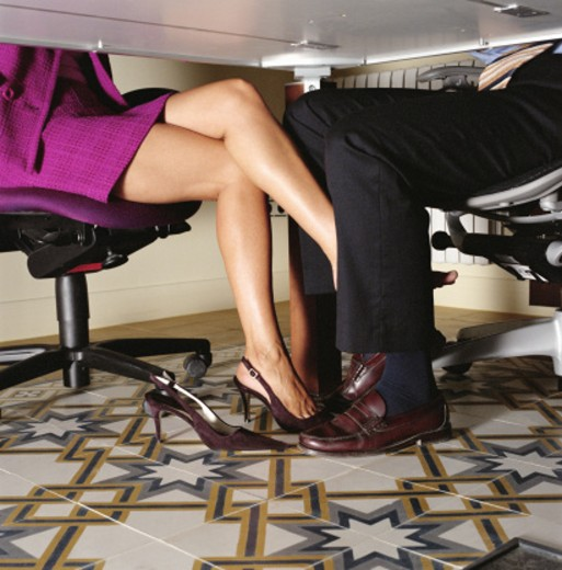 Stock Photo: 1527R-1120077 Businesswoman rubbing foot against businessman's leg, low section
