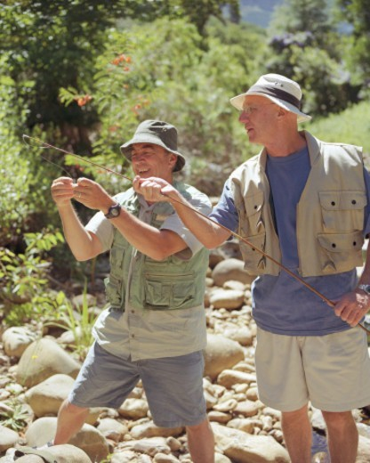 Two mature men with fishing rod, one adjusting fly : Stock Photo