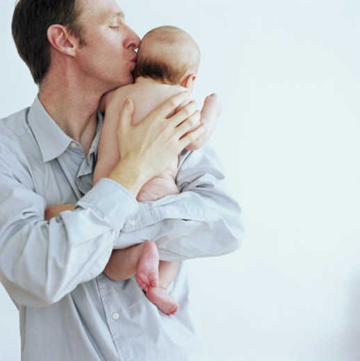 Father kissing baby girl (3-6 months) on head : Stock Photo