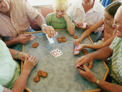 Three generational family gathered around table playing card game : Stock Photo