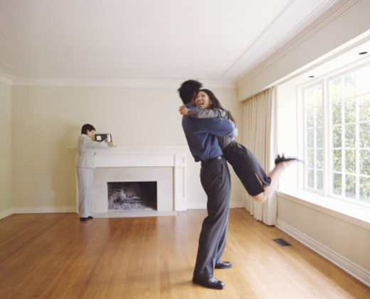 Stock Photo: 1527R-1121866 Couple embracing in new house, mature female realtor in background