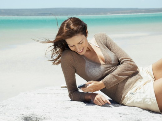 Woman relaxing on rock by sea, looking down at mobile phone, smiling : Stock Photo