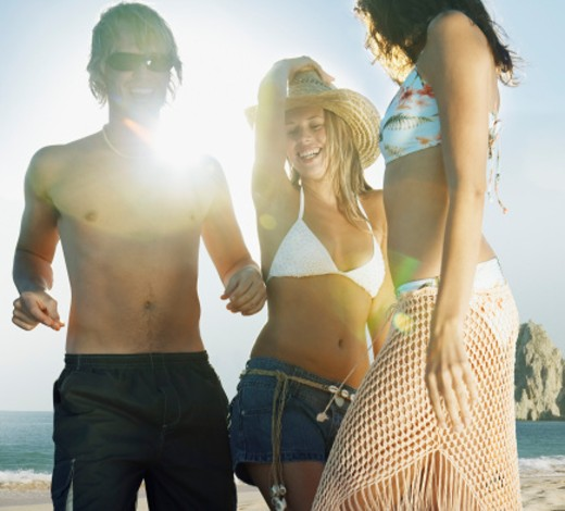 Stock Photo: 1527R-1122046 Three young friends dancing on beach, smiling (sun flare)