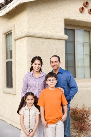 Stock Photo: 1527R-1122241 Parents in front of house with son and daughter (5-10), portrait