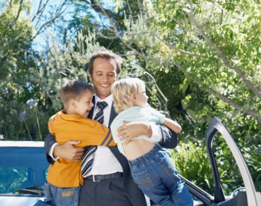 Father in suit embracing children (3-5) by car, smiling : Stock Photo