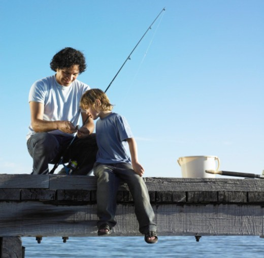 Stock Photo: 1527R-1123271 Father showing son (4-6) how to bait fishing hook on jetty, smiling