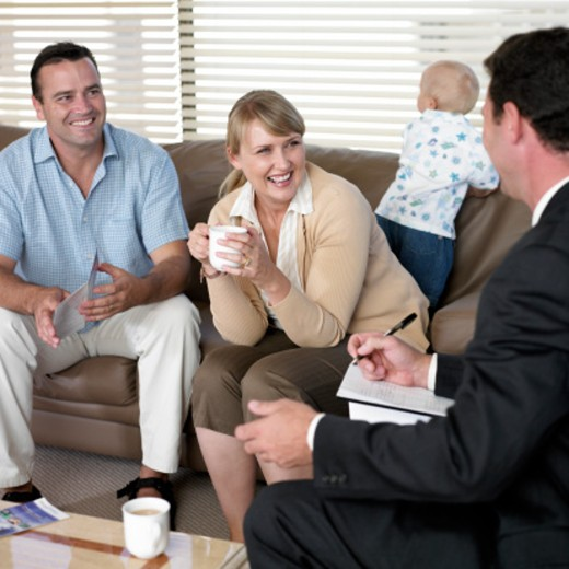 Stock Photo: 1527R-1123373 Couple on sofa with baby boy (12-15 months) smiling at businessman