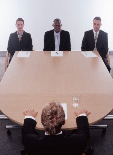 Businessman facing businesswoman and two businessmen in meeting : Stock Photo