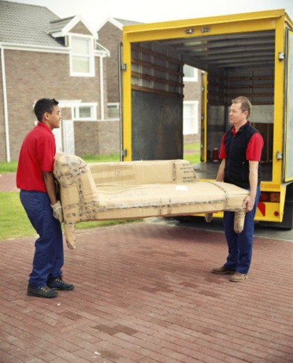 Two removal men carrying chaise longue covered in cardboard : Stock Photo