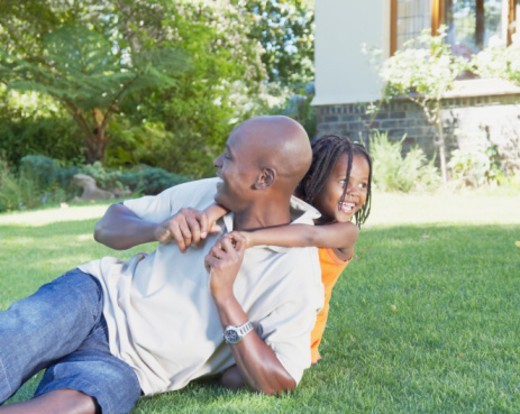 Girl (3-5) on grass with arms around father's neck, smiling : Stock Photo