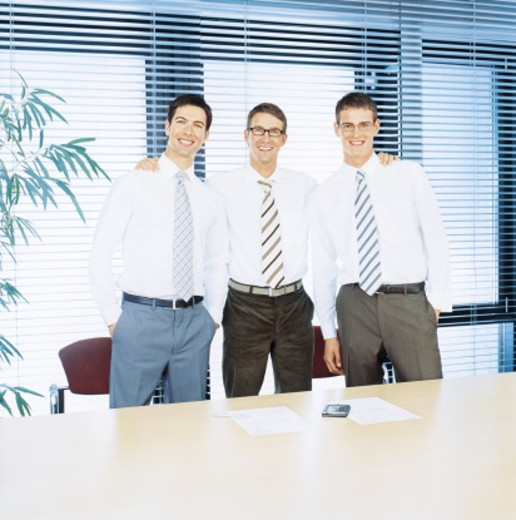 Three businessmen standing by conference table, smiling, portrait : Stock Photo