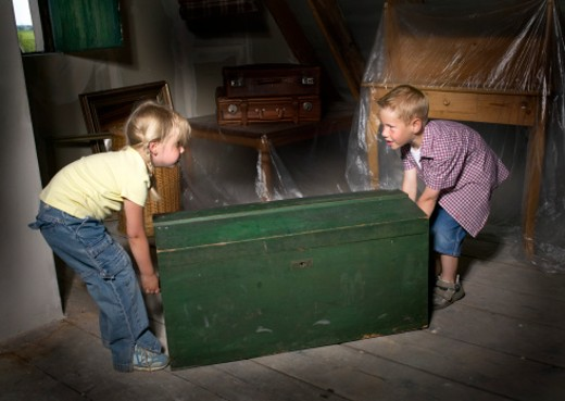 Boy and girl (4-6) preparing to lift green box indoors : Stock Photo