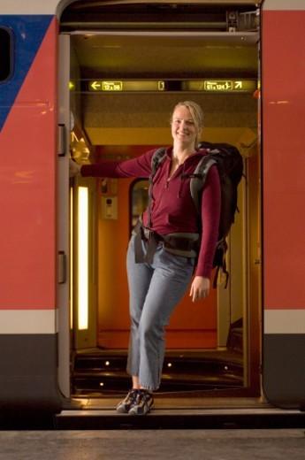 Woman with backpack standing in open doorway of train, portrait : Stock Photo