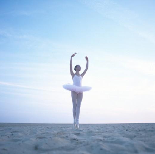 Teenage ballerina (16-18) performing pirouette on beach, ground view : Stock Photo