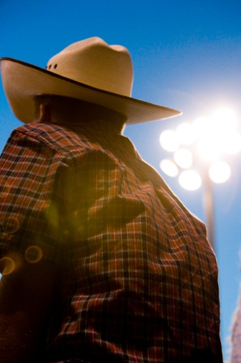 Cowboy with arena lights over shoulder, rear view, close-up : Stock Photo