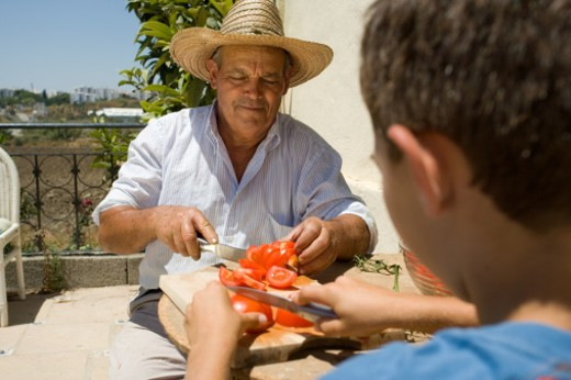 Senior man and grandson (8-10) cutting tomatoes on chopping board : Stock Photo
