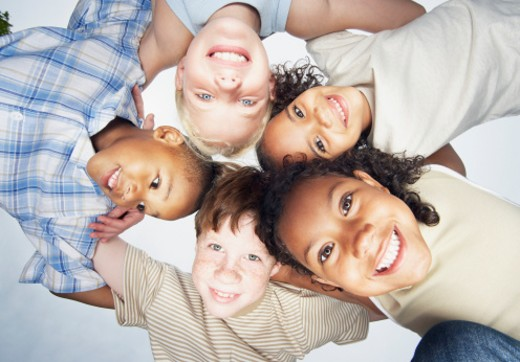 Stock Photo: 1527R-1126627 Group of children (5-10) in huddle, view from below, smiling, portrait