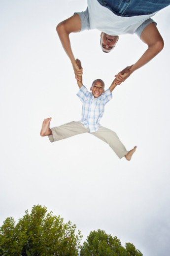 Father swinging son (4-6), view from below, smiling, portrait of boy : Stock Photo