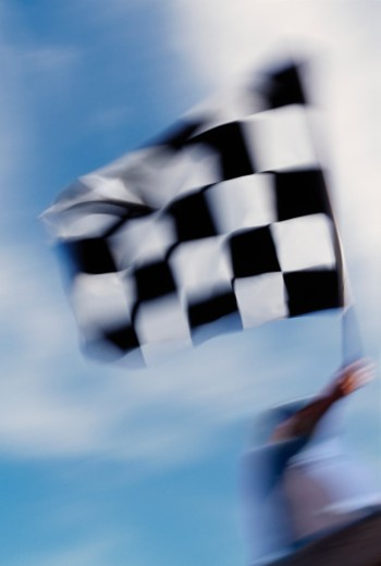 Auto race official waving checkered flag (blurred motion) : Stock Photo