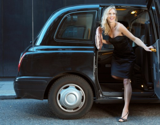 Stock Photo: 1527R-1127734 Young woman in evening dress, exiting taxi, smiling