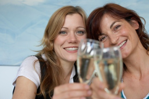 Two women toasting with glasses of wine (focus on faces) : Stock Photo