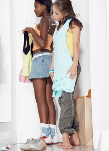 Two teenage girls (13-15) holding clothes on hangers in change room : Stock Photo
