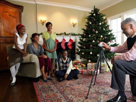 Grandfather photographing grandchildren (11-15) beside Christmas tree : Stock Photo
