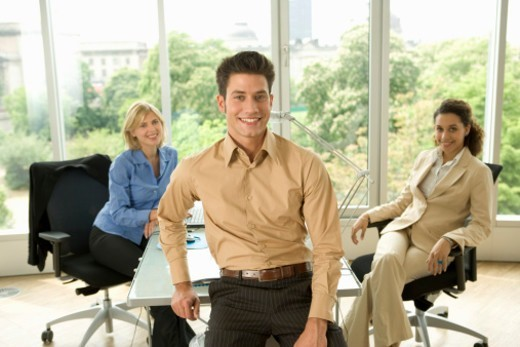 Stock Photo: 1527R-1128610 Businessman and two businesswomen in office, smiling, portrait