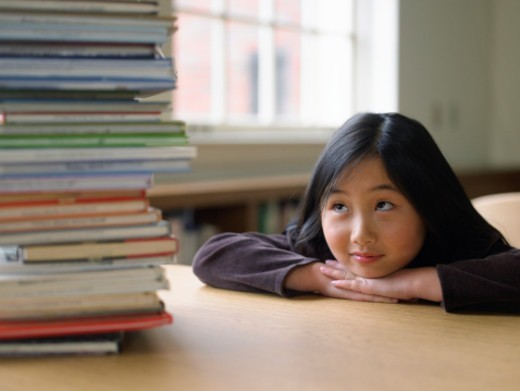 Girl (7-9) looking at stack of books on desk, resting chin on hands : Stock Photo