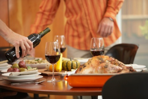 Two men setting table (focus on man pouring red wine in foreground) : Stock Photo