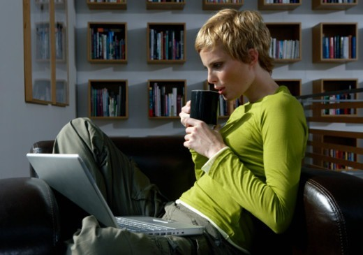Woman in armchair drinking from mug, laptop computer on lap, side view : Stock Photo